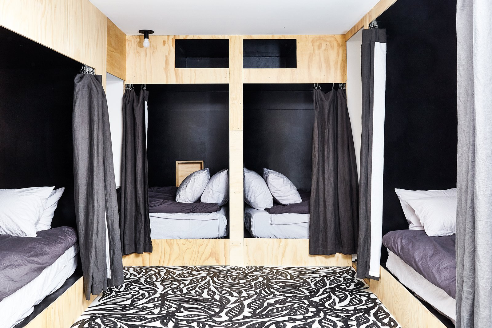 """Bedroom, Bed, Ceiling, and Bunks The basement has been partially finished into a """"bunk room"""" with four twin bed nooks built into the walls. The basement includes a small lounge area with its own TV.  Bedroom Bed Ceiling Bunks Photos from Get Cozy in This Renovated A-Frame Cabin in the Woods"""