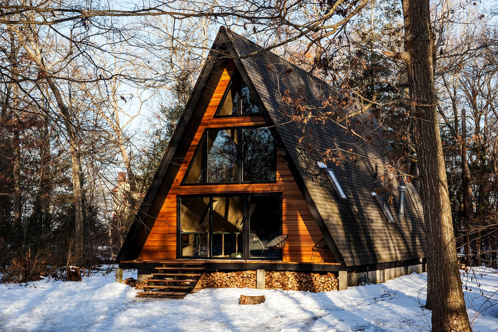 Exterior, Mid-Century Building Type, A-Frame RoofLine, Wood Siding Material, Shingles Roof Material, House Building Type, and Cabin Building Type The material palette consists of concrete, bleached flooring, pine plywood, and lots of matte black and white.