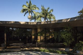 The roof is a low and flat sinuous slab. , and a curved volume of the rooms, sets up a T plan that defines the project.