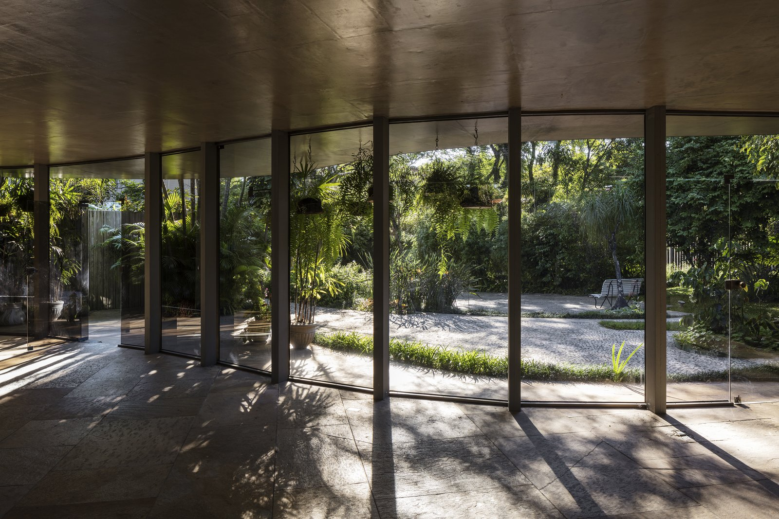 Outdoor, Gardens, Walkways, Shrubs, Trees, and Garden The main living space opens to a lush tropical garden.  Photo 1 of 6 in A Modern Concrete Retreat by Oscar Niemeyer Is Available For the First Time