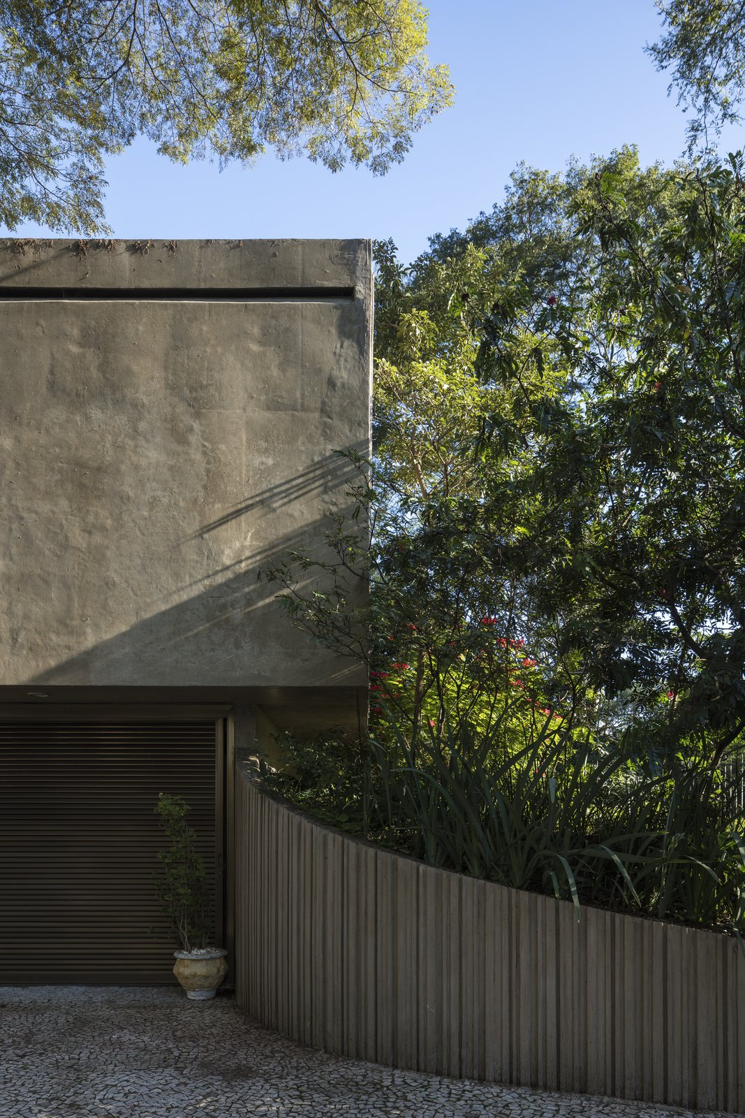 Exterior, House Building Type, Flat RoofLine, and Concrete Siding Material A hovering monolithic concrete volume forms the bedroom wing and covers the carport.  Photo 4 of 6 in A Modern Concrete Retreat by Oscar Niemeyer Is Available For the First Time