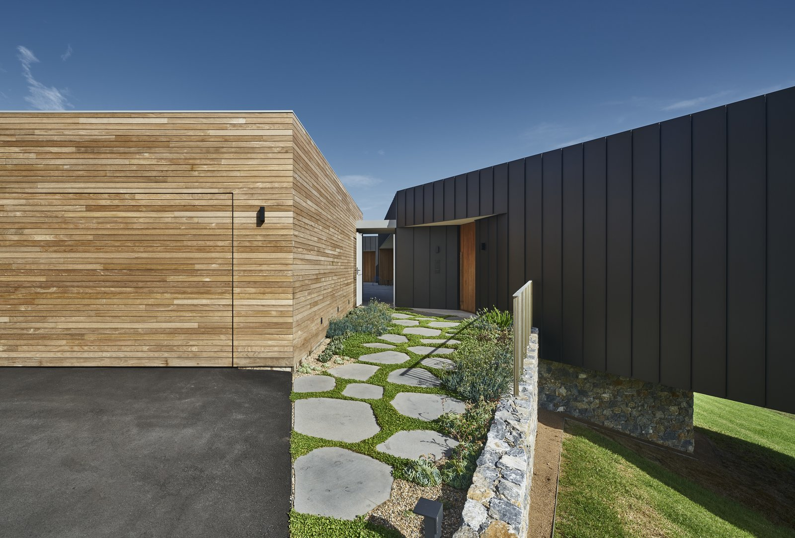 Garage and Detached Garage A wood-clad garage sits adjacent to the home.  Best Garage Photos from An Australian Abode Fuses Structure With Scenery