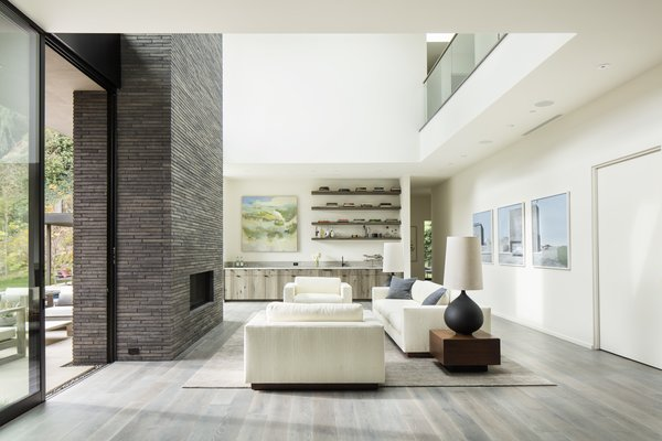 The living room features a double-height ceiling and anchored by the dual indoor-outdoor fireplace.