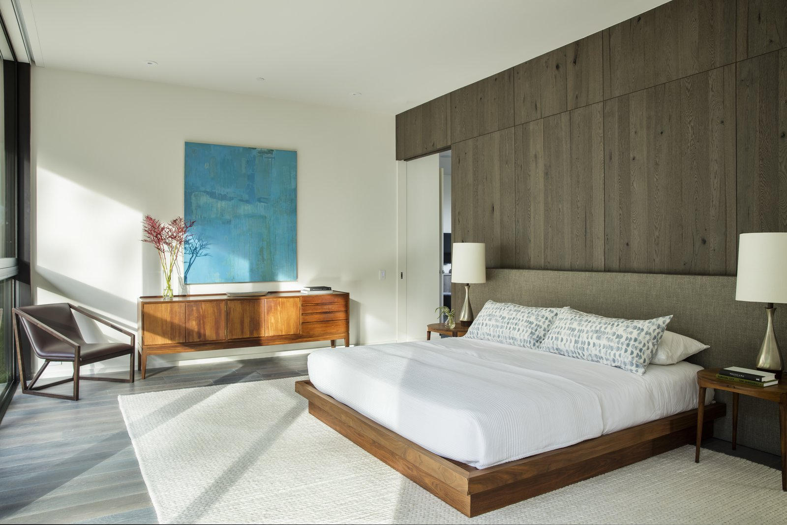 Bedroom, Bed, Medium Hardwood Floor, Chair, Night Stands, Rug Floor, Table Lighting, and Recessed Lighting One of the upstairs bedrooms.  Photo 9 of 13 in Live Large in This Marmol Radziner–Designed Home That's Asking $16.9M