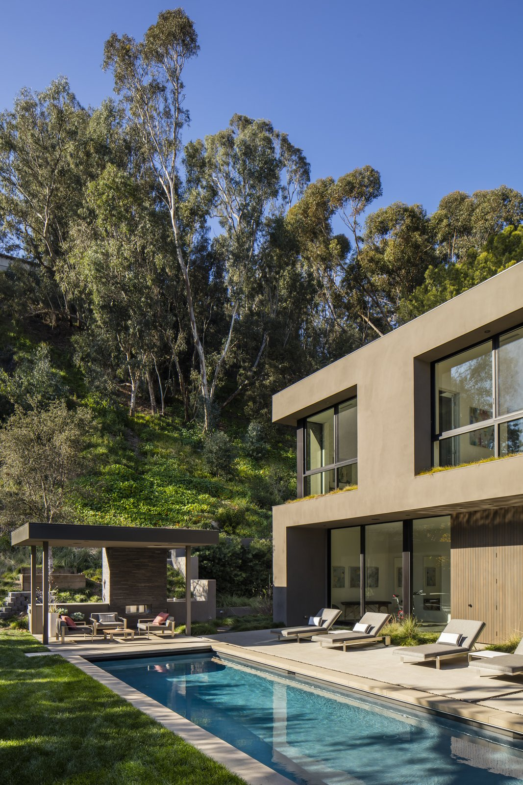 Outdoor, Large Patio, Porch, Deck, Lap Pools, Tubs, Shower, Trees, Back Yard, Grass, and Concrete Patio, Porch, Deck The pool area also features an outdoor kitchen.  Photo 3 of 13 in Live Large in This Marmol Radziner–Designed Home That's Asking $16.9M