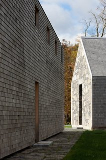 The elongated, gabled house is clad in cedar shingles and features massive end walls that have been crafted from Lake Champlain bedrock.
