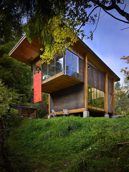 The home hovers above the ground on concrete bases, so as not to intrude too heavily on the natural landscape. Note the red hatch door from the loft bedroom that can be lowered.