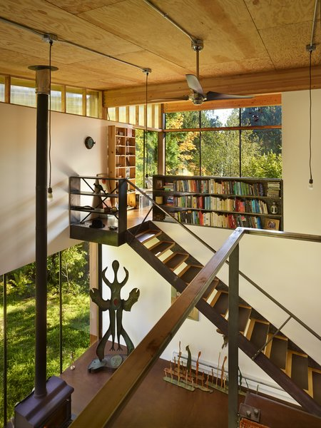 The double-height interior features a kitchen and living area on the ground level with a sleeping loft above.