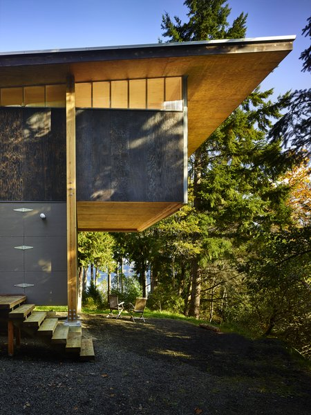 The home's minimalist construction includes a mix of unfinished and charred plywood to form a simple two-story volume with a slightly sloping roof and cantilevered bedroom loft with clerestory windows made from polycarbonate panels.