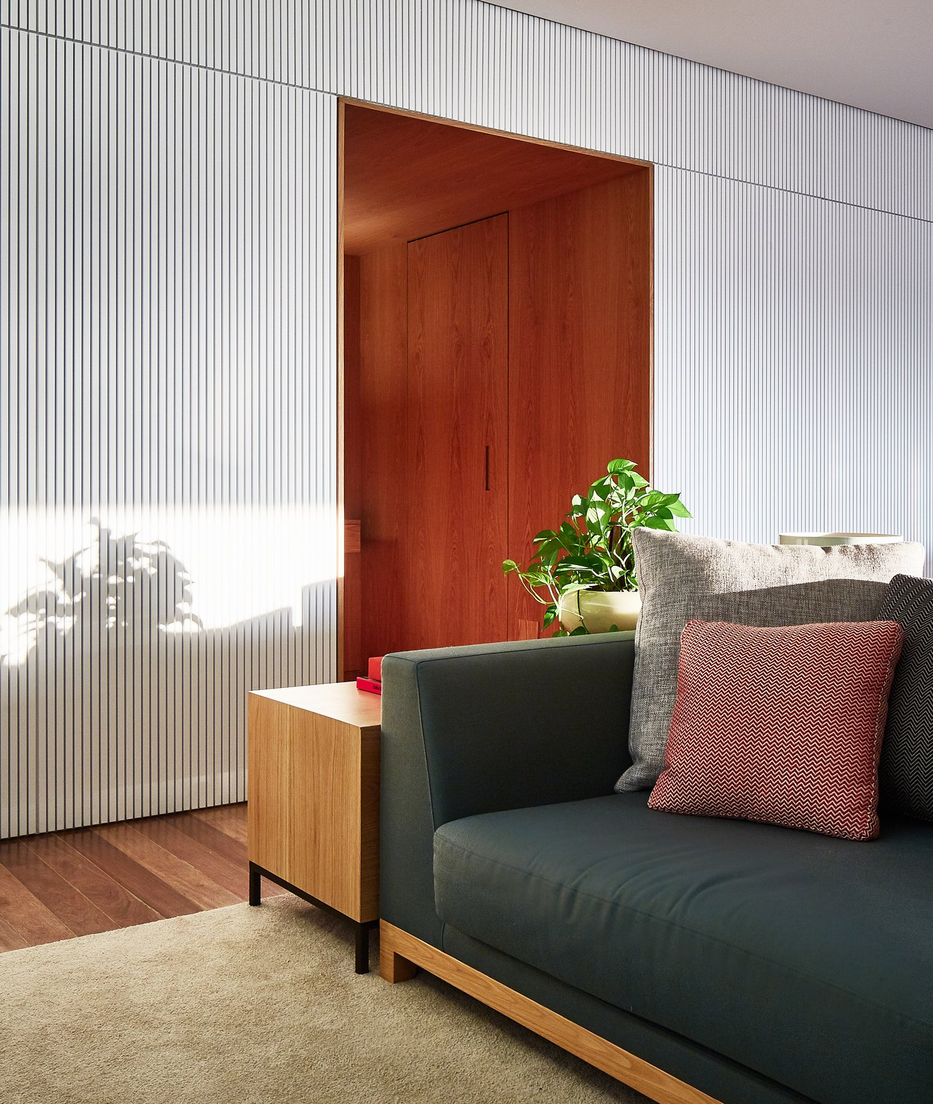 Living Room, End Tables, Medium Hardwood Floor, Rug Floor, and Sofa A wood-clad entrance hall leads to the bedrooms.  Photo 2 of 17 in Color Unites With Texture to Make This Brazilian Abode Appear Much Larger and Brighter