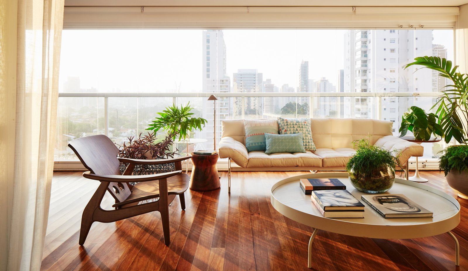 Living Room, Medium Hardwood Floor, Table Lighting, End Tables, Lamps, Coffee Tables, Chair, and Sofa City views courtesy of large windows which also provide ample natural light.  Photo 10 of 17 in Color Unites With Texture to Make This Brazilian Abode Appear Much Larger and Brighter