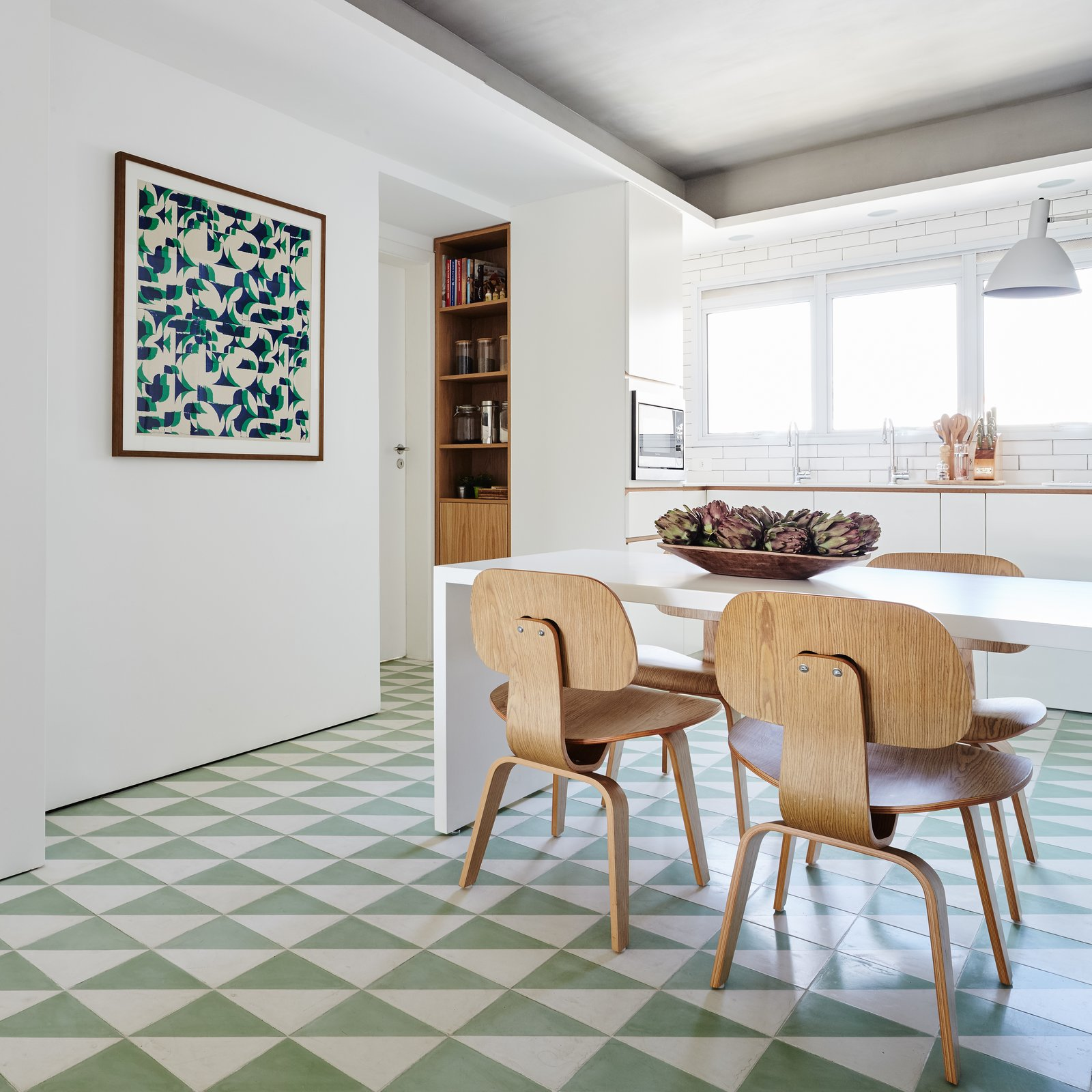 Kitchen, Wall Lighting, Microwave, White Cabinet, and Ceramic Tile Floor The kitchen is large enough for an eat-in  Photo 7 of 17 in Color Unites With Texture to Make This Brazilian Abode Appear Much Larger and Brighter