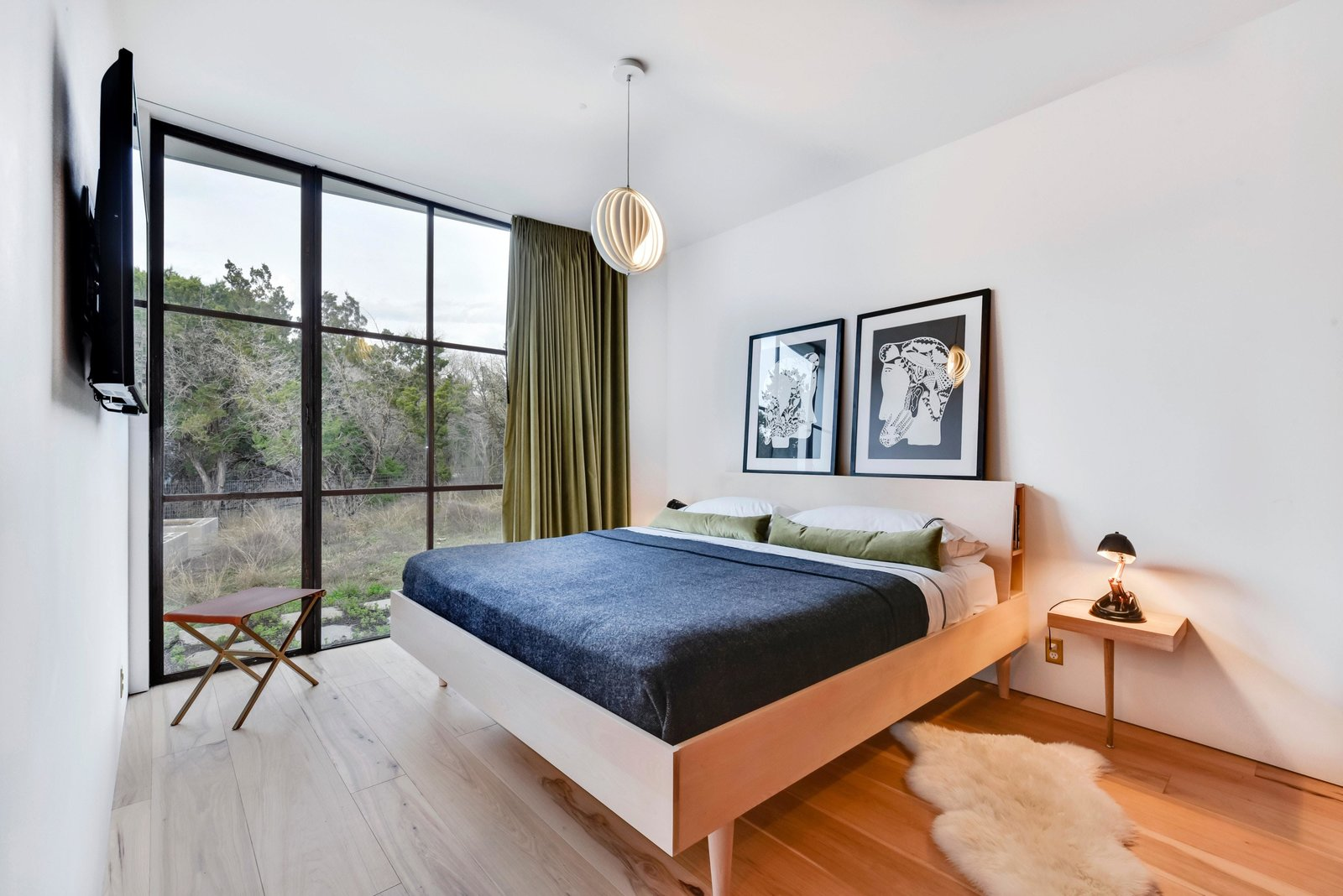 Bedroom, Bed, Pendant Lighting, Medium Hardwood Floor, Night Stands, Table Lighting, and Rug Floor Another bright and minimalist bedroom.  Photo 9 of 22 in Own This Alluring Sculptural Abode in Austin For $3.1M