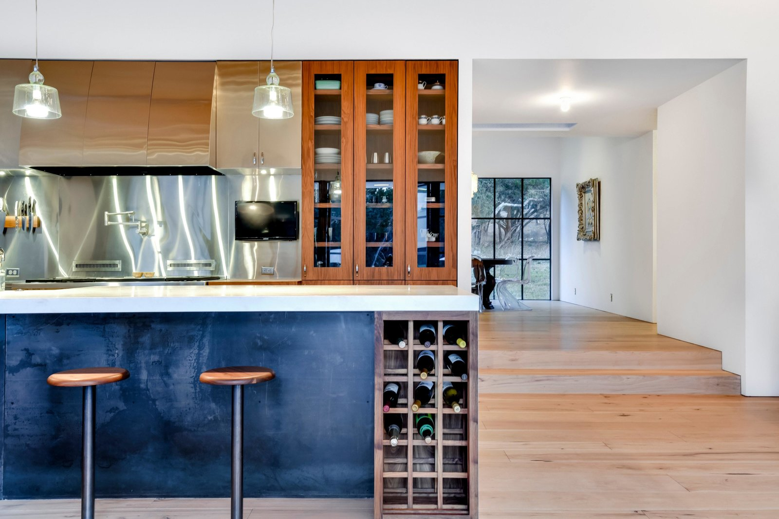 Kitchen, Metal, Range Hood, Range, Medium Hardwood, Wood, Pendant, Beverage Center, and Metal A few steps lead to a more formal dining area.  Kitchen Metal Range Hood Beverage Center Photos from Own This Alluring Sculptural Abode in Austin For $3.1M
