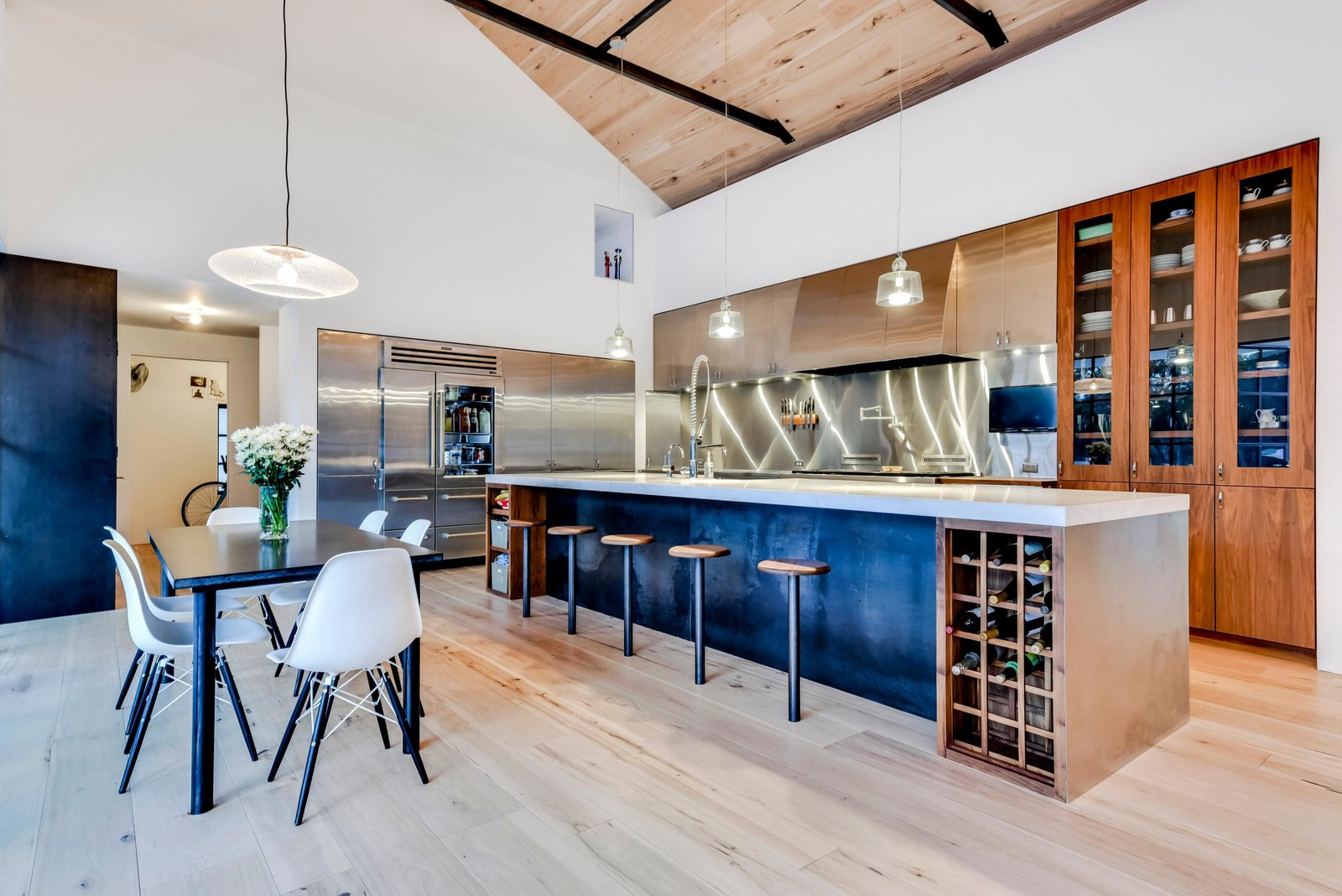 Kitchen, Medium Hardwood, Range Hood, Wall Oven, Drop In, Metal, Metal, Range, Wood, Pendant, Refrigerator, and Beverage Center The kitchen and dining area from the other angle.  Kitchen Metal Range Hood Metal Photos from Own This Alluring Sculptural Abode in Austin For $3.1M