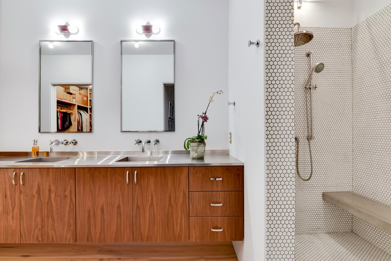 Bath, Medium Hardwood, Open, Wall, Mosaic Tile, Drop In, and Metal The home features four-and-a-half baths. This one with two sinks and an open penny-tile shower area.  Bath Mosaic Tile Medium Hardwood Wall Open Photos from Own This Alluring Sculptural Abode in Austin For $3.1M