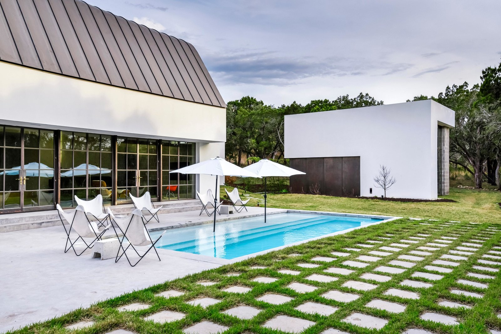 Outdoor, Back Yard, Grass, Large Patio, Porch, Deck, and Small Pools, Tubs, Shower The studio seen in the backgroud here, is adjacent to the home.  Photo 20 of 22 in Own This Alluring Sculptural Abode in Austin For $3.1M