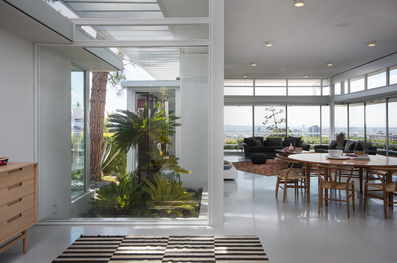Living Room, Table, Chair, Ceiling Lighting, Console Tables, and Rug Floor Ample glazing provides a strong sense of indoor/outdoor living.  Best Photos from Rooney Mara Asks $3.45M For a Restored Midcentury Stunner in L.A.