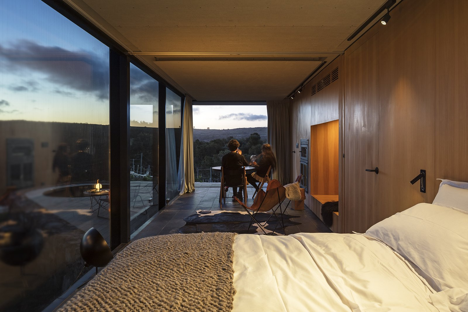 Bedroom, Bed, Slate Floor, Chair, and Track Lighting The nightscape is equally stunning.  Best Photos from A New Prefab Hotel in Uruguay Seems to Melt Into the Landscape