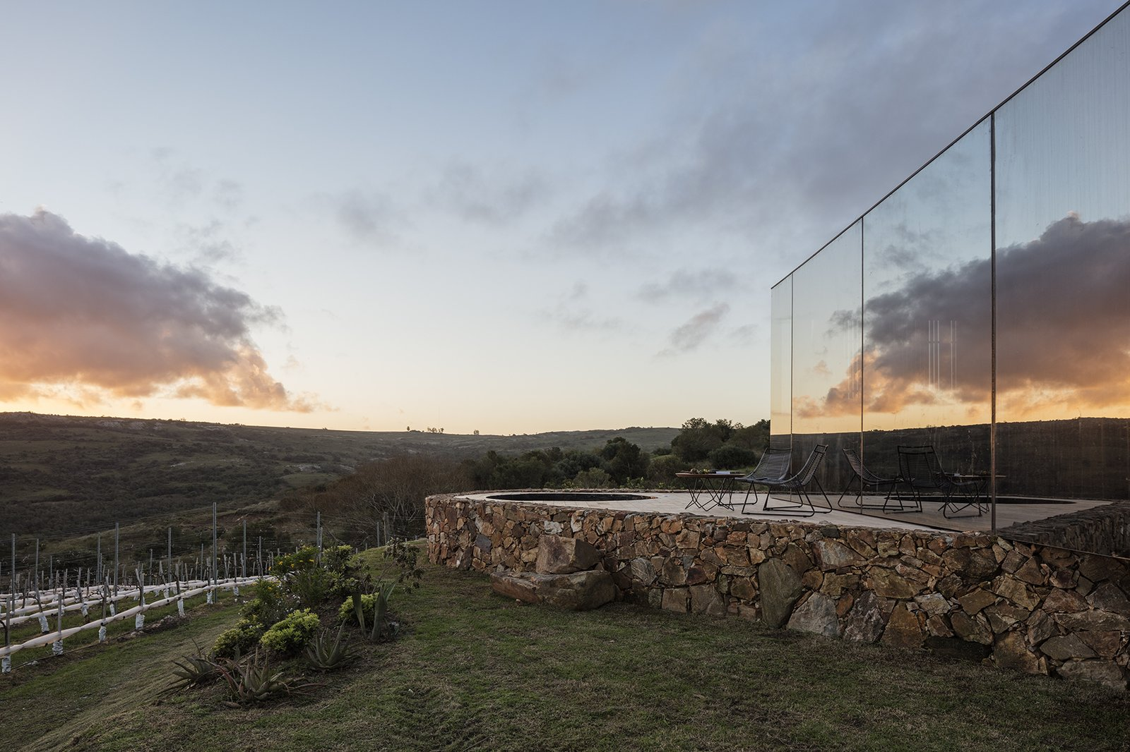 Outdoor, Grass, Field, Small Patio, Porch, Deck, and Shrubs The mirrored structures are inserted into the landscape  Best Photos from A New Prefab Hotel in Uruguay Seems to Melt Into the Landscape