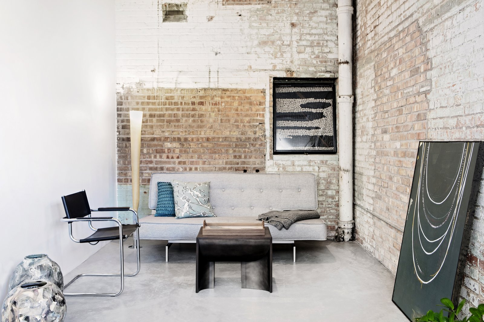 Living Room, Sofa, Coffee Tables, Concrete Floor, Chair, and Floor Lighting A den-like nook with a sofa in the corner.  Photo 17 of 29 in Before & After: A Rundown Bodega in Chicago Is Reimagined Into a Vibrant Live/Work Space