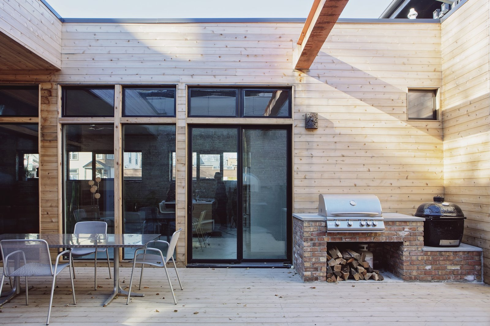 Outdoor, Side Yard, Wood Patio, Porch, Deck, and Small Patio, Porch, Deck Cedar siding elevates the look of the center courtyard which is a perfect spot for entertaining.  Photo 9 of 29 in Before & After: A Rundown Bodega in Chicago Is Reimagined Into a Vibrant Live/Work Space
