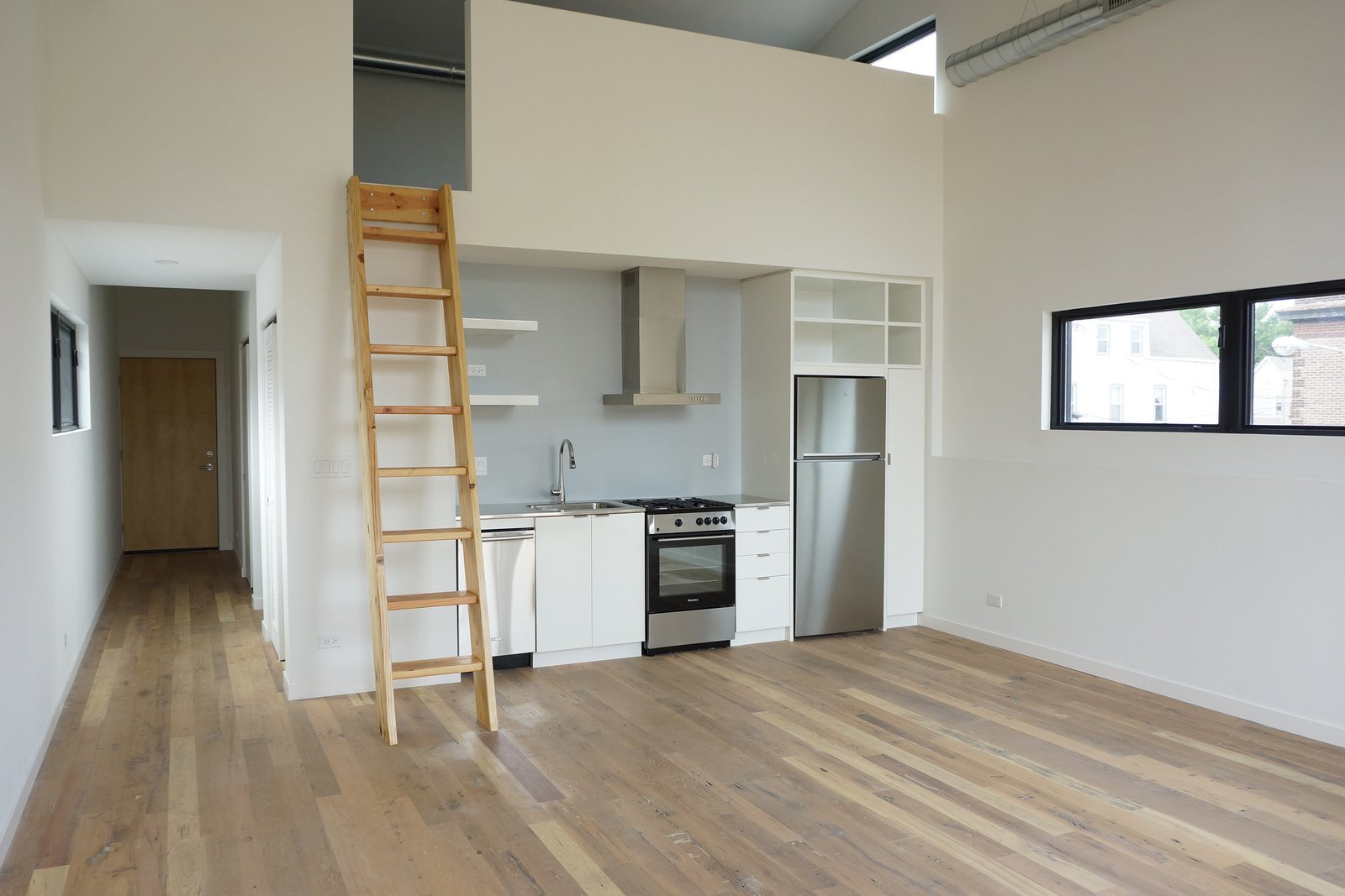 Kitchen, Drop In Sink, Medium Hardwood Floor, Range, White Cabinet, Refrigerator, Range Hood, and Wall Oven The one bedroom loft apartment has a private deck (also clad in cedar), which allows for access to natural light. Custom, modern cabinets optimize kitchen space, and a custom ladder leads to the loft that overlooks the open living space. The reclaimed wood floors that are a mix of oak, walnut, and other hardwoods that have been restored and repurposed from local Illinois barns to provide sustainable and durable flooring.  Photo 22 of 29 in Before & After: A Rundown Bodega in Chicago Is Reimagined Into a Vibrant Live/Work Space