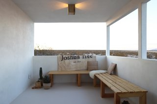 "Qn the opposite end of the covered patio the Smirkes built two long benches that overlook the open desert. The canvas is a flag they had made by Lindsay Smith of Makers Workshop that says, ""Joshua Tree Est. 1957"" the year the original cabin was constructed."