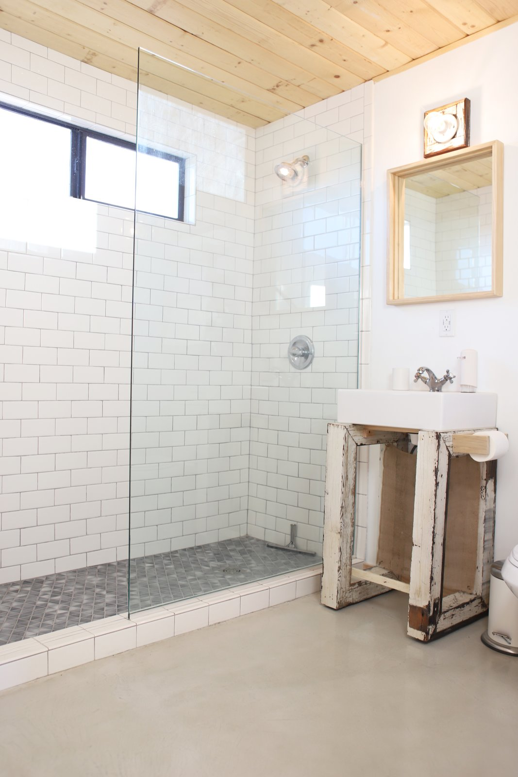 Bath, Pedestal, Subway Tile, Full, Open, and Wall A glass-enclosed shower helps increased the sense of space in the tiny bathroom.  Best Bath Subway Tile Open Photos from A Couple Buy a Collapsing Cabin For $7K in Joshua Tree and Revamp it Into a Desert Oasis