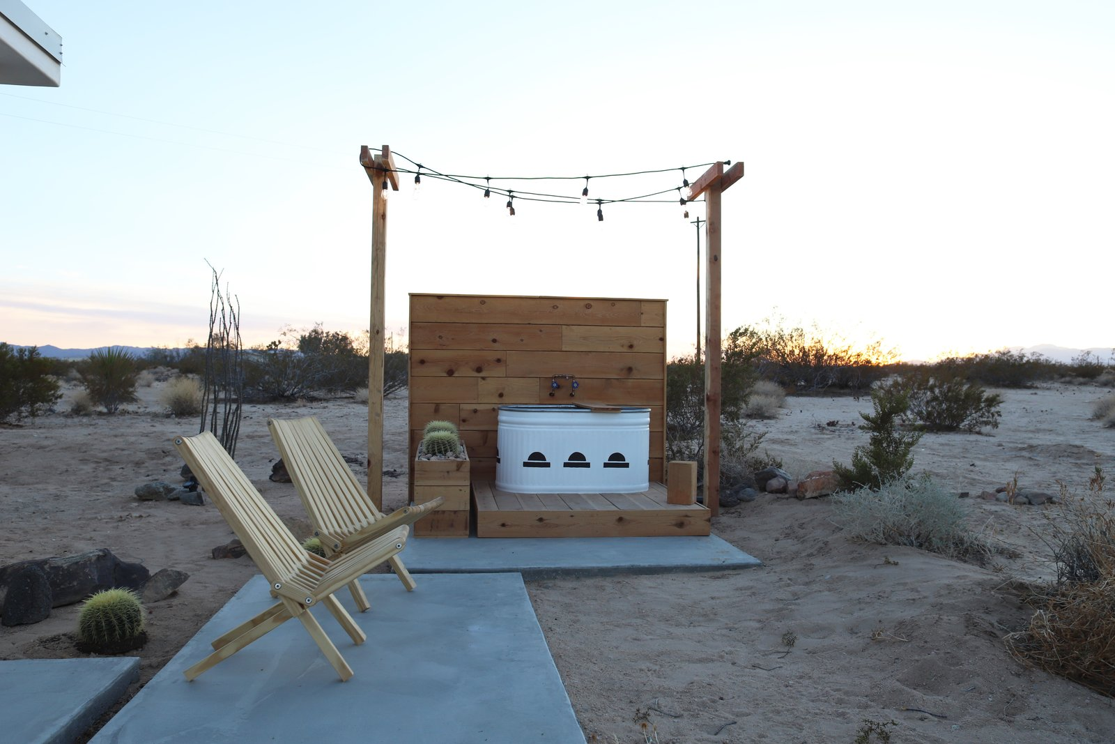 Outdoor, Desert, Small, Concrete, Shrubs, Back Yard, Plunge, Horizontal, Hanging, Wood, and Hot Tub The addition of an alfresco tub is perfect for relaxing on starry desert evenings.  Outdoor Concrete Plunge Small Photos from A Couple Buy a Collapsing Cabin For $7K in Joshua Tree and Revamp it Into a Desert Oasis