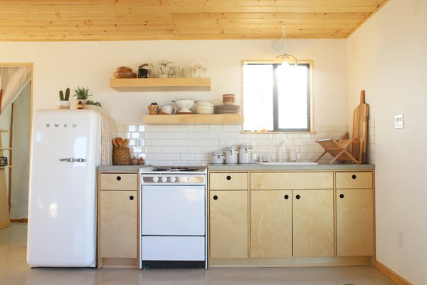 Kitchen, Range, Subway Tile, Drop In, Refrigerator, Wood, Wall, and Wall Oven The petite open kitchen is....  Best Kitchen Wall Oven Range Wall Photos from A Couple Buy a Collapsing Cabin For $7K in Joshua Tree and Revamp it Into a Desert Oasis