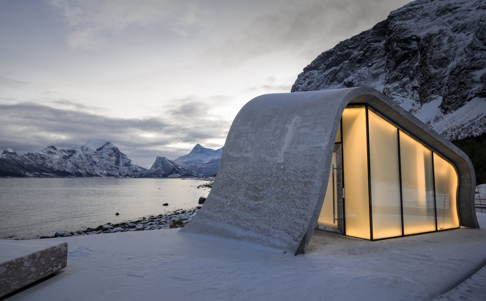 Exterior, Curved RoofLine, Glass Siding Material, and Concrete Siding Material The wave-shaped structure glows from within.  Photo 8 of 9 in This Concrete Rest Stop Will Make You Want to Visit Norway