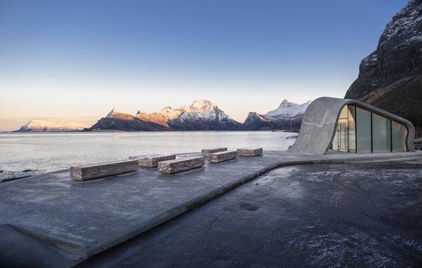 A large poured concrete terrace faces the sea.
