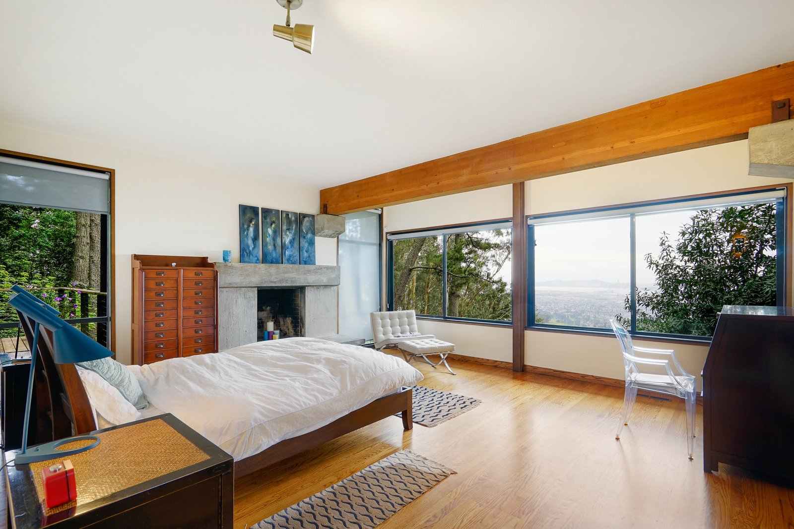 Bedroom, Ceiling Lighting, Medium Hardwood Floor, Bed, Dresser, Night Stands, Rug Floor, and Chair The master suite looks out onto the waters of the Bay.  Photo 12 of 17 in This Knockout Midcentury in the Bay Area Will Run You $1.9M
