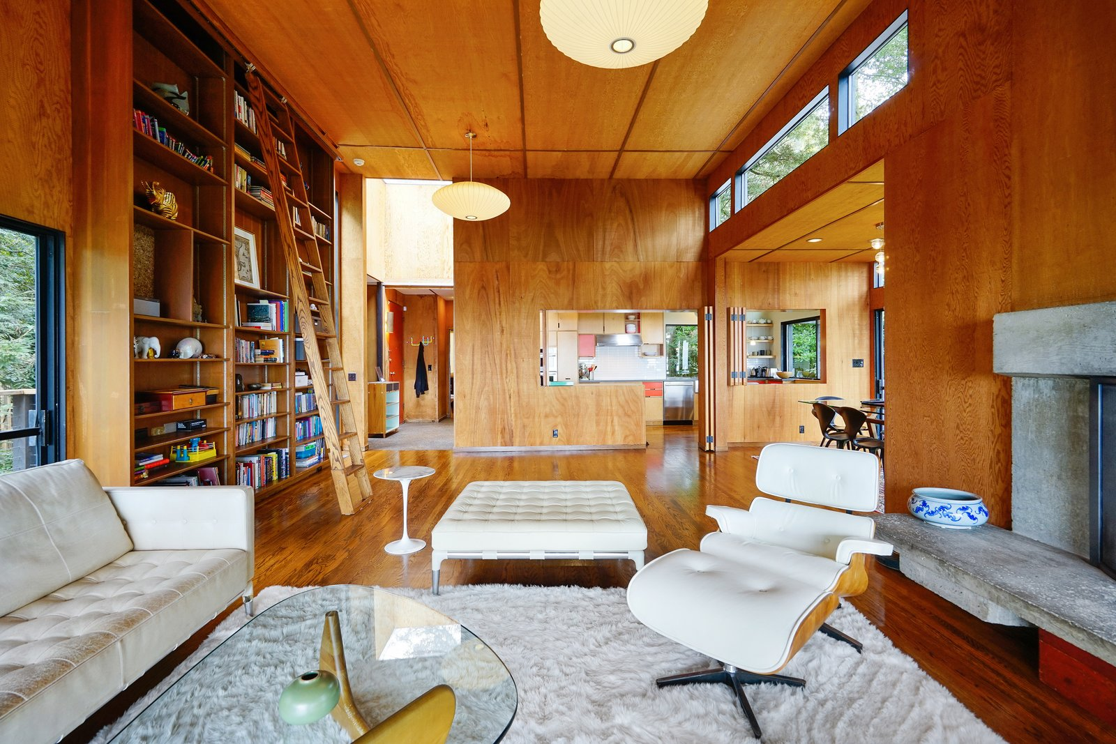 Living, Storage, Sofa, Ottomans, Coffee Tables, End Tables, Shelves, Standard Layout, Wood Burning, Chair, Medium Hardwood, Rug, Pendant, and Recessed The living room boasts original wood paneled ceiling and walls, and beautiful built-in bookshelves.  Living Ottomans Shelves Standard Layout Photos from This Knockout Midcentury in the Bay Area Will Run You $1.9M