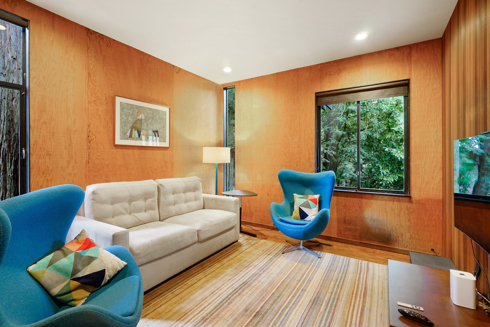 Living Room, Sofa, Chair, Rug Floor, Medium Hardwood Floor, End Tables, Floor Lighting, and Recessed Lighting A sitting room.  Photo 11 of 17 in This Knockout Midcentury in the Bay Area Will Run You $1.9M