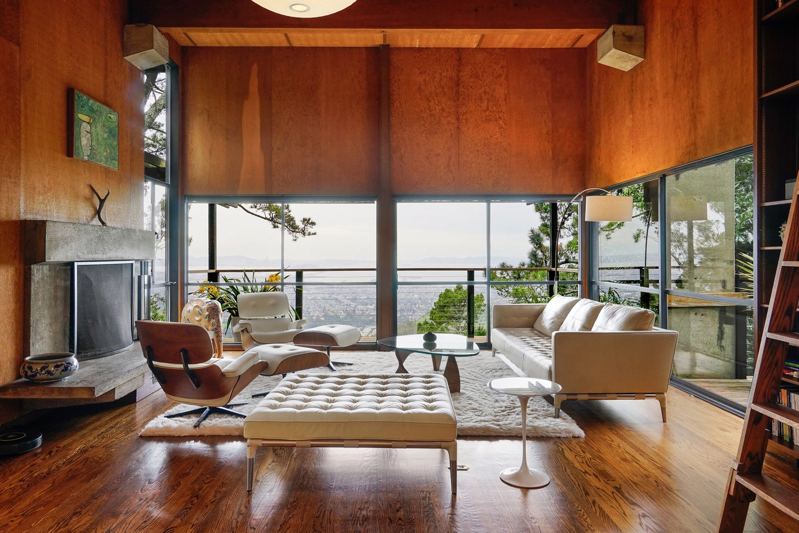 Living, Sofa, Chair, Standard Layout, End Tables, Coffee Tables, Medium Hardwood, Wood Burning, Ottomans, Floor, Shelves, and Pendant The living room takes full advantage of the homes' stunning views.  Living Ottomans Shelves Standard Layout Photos from This Knockout Midcentury in the Bay Area Will Run You $1.9M