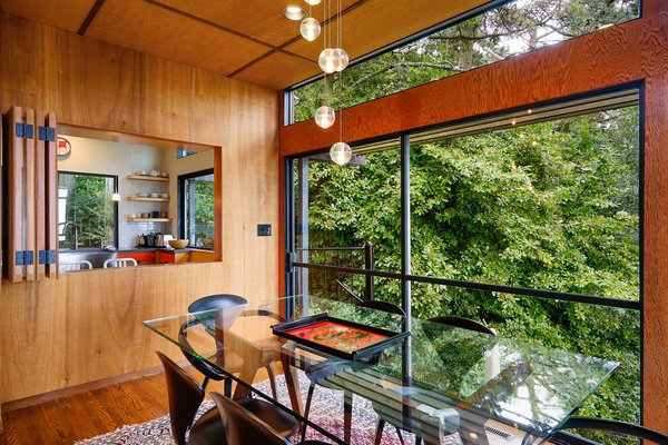 Dining Room, Medium Hardwood Floor, Table, Chair, Rug Floor, Recessed Lighting, and Pendant Lighting A peek into the kitchen.  Photo 8 of 17 in This Knockout Midcentury in the Bay Area Will Run You $1.9M