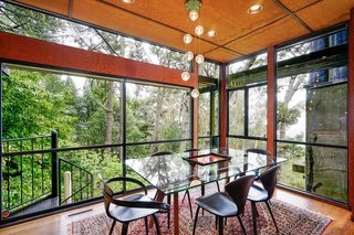 The dining room has the sense of being in a glass-enclosed structure in the woods.