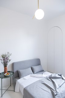 A bedroom/living room includes a sofa-bed, a small side table, and some arched-shaped closet space.
