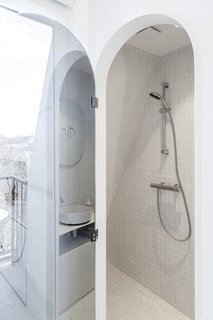 The bathroom features light grey tiles, a shower, sink, and toilet.