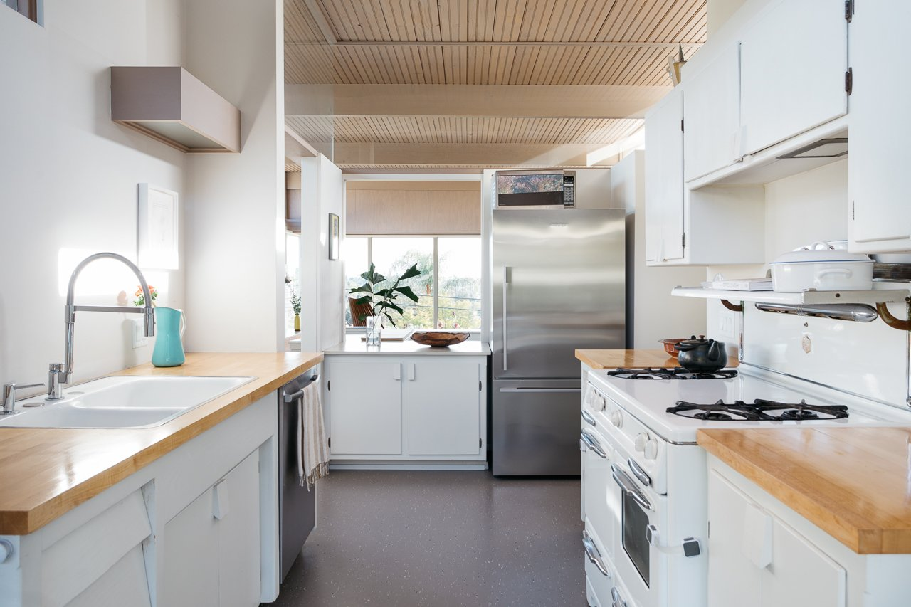 Kitchen, White Cabinet, Refrigerator, Range, Drop In Sink, Wood Counter, Terrazzo Floor, Wall Oven, and Dishwasher The kitchen is opposite the dining area.  Best Photos from Own a Charismatic L.A. Midcentury Designed by Rudolph Schindler For $1.8M