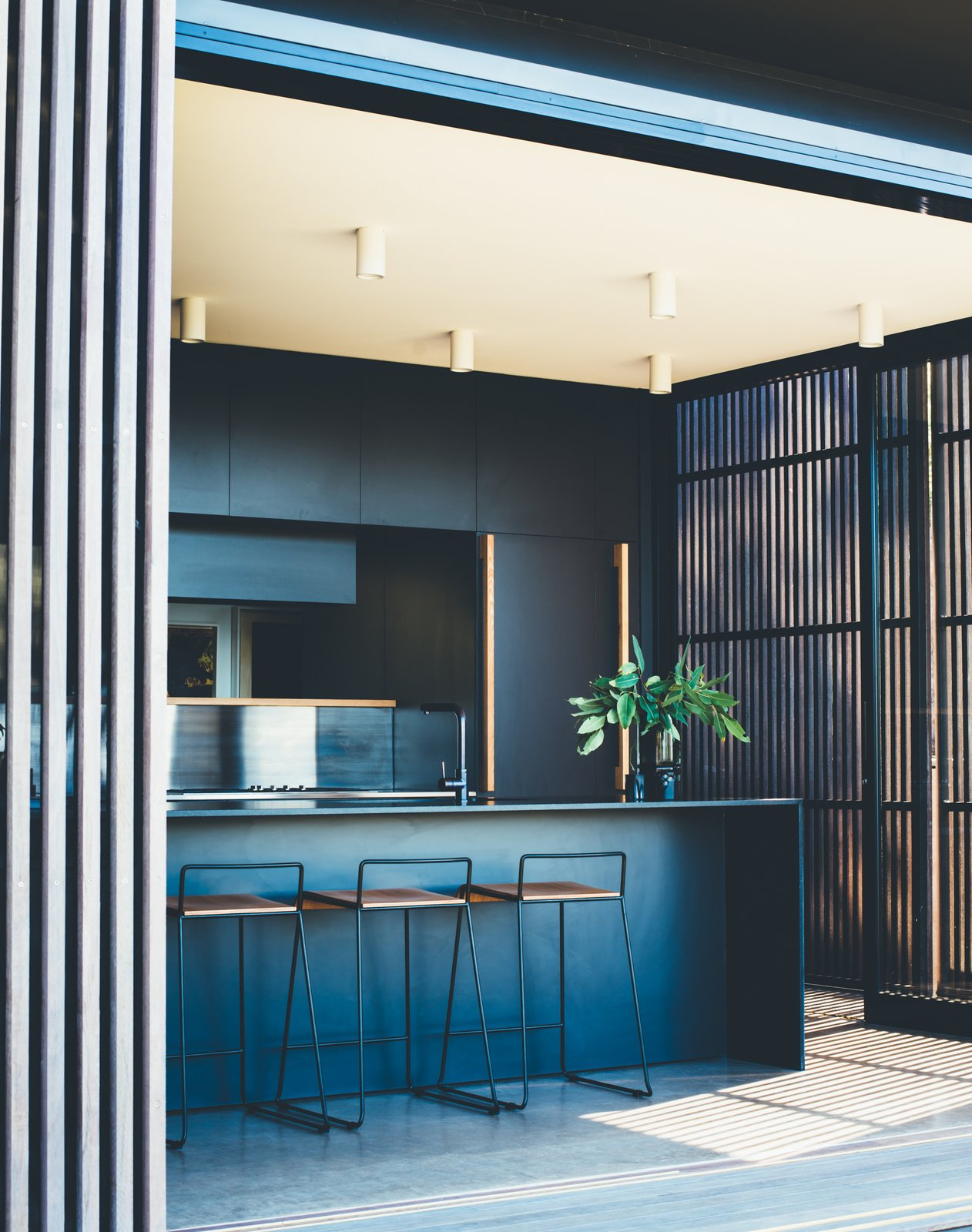 Kitchen, Ceiling, Laminate, Drop In, and Concrete The building is kept low to the ground, so you can step directly from the house into the garden.  Best Kitchen Laminate Ceiling Photos from This Australian Abode Is a Glass Pavilion Wrapped in Sliding Hardwood Screens