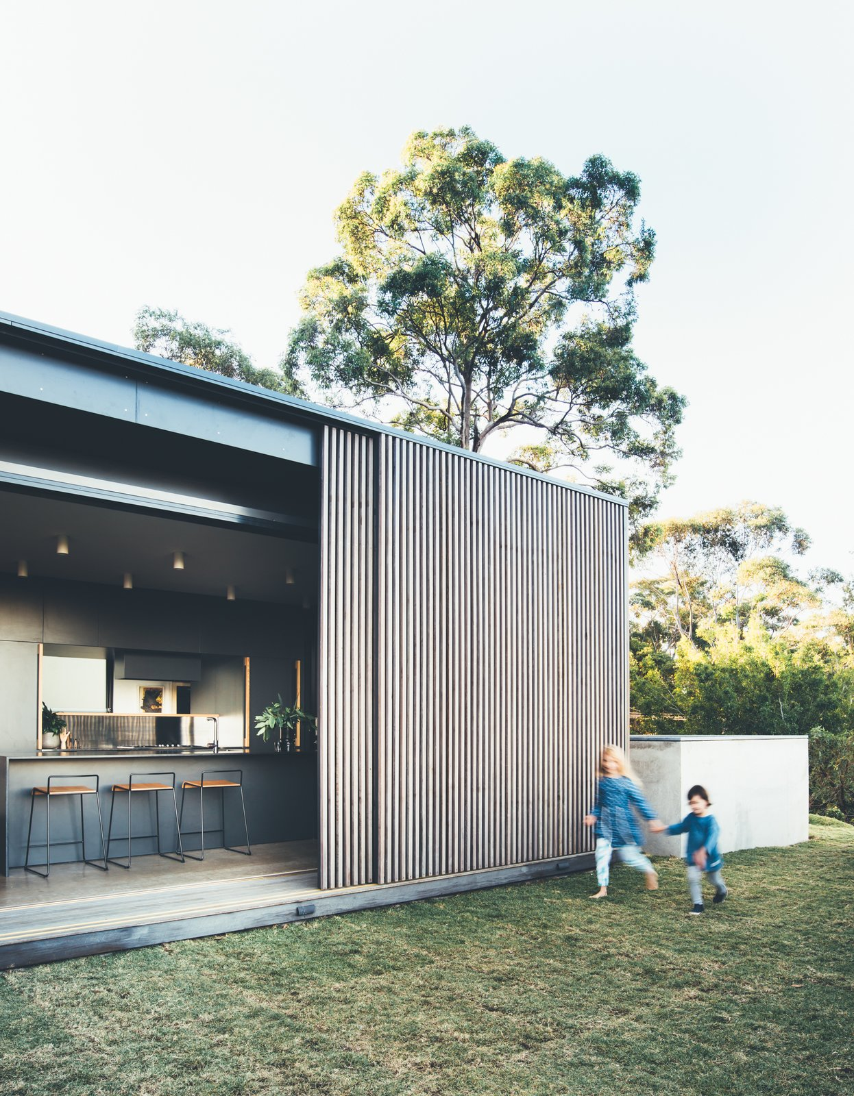 Exterior, House Building Type, Wood Siding Material, and Flat RoofLine During the winter, the family can slide the screens open to let in the winter sun, in summer they can close the screens to provide shade, while still maintaining views and breezes through the timber battens.  Best Photos from This Australian Abode Is a Glass Pavilion Wrapped in Sliding Hardwood Screens