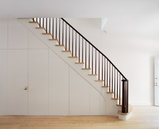 The main staircase at the center of the house creates a gracious ascent from the open living room and kitchen at the parlor level to a library and bedrooms on the upper levels. The stained walnut handrail adds a traditional look, but boasts a clean, modern treatment. Wood paneling envelops a discreet door that leads to the cellar.