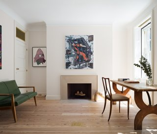 The focal point of the study is a custom-designed limestone fireplace and the artwork above it.
