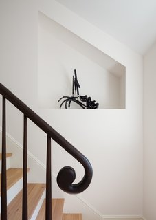 Yun designed this curved handrail. To the side, a carved niche is meant to showcase art.