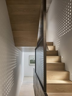 A perforated steel plate forms a wall between the staircase and the room.