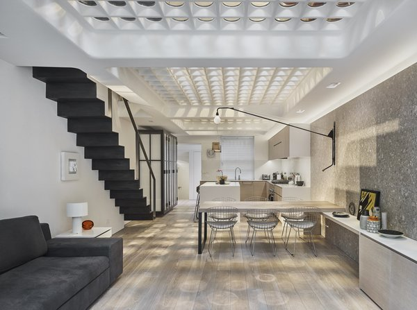 The dappled light brightens the basement which houses the kitchen and an open-plan living and dining area.