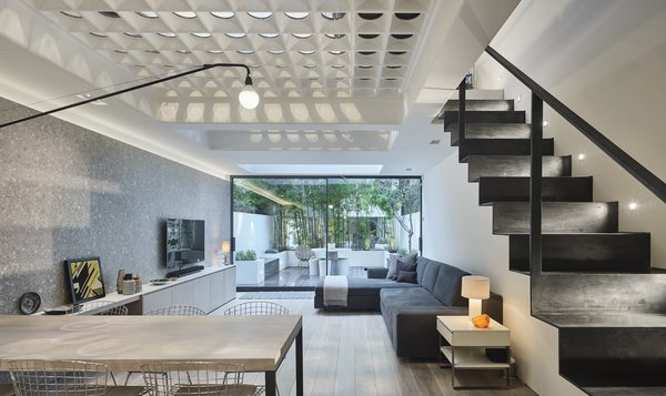 Thanks to the glass perforations connecting the first two levels of the home, the structure no longer suffers from a dark, gloomy interior. The team also incorporated a handmade steel staircase to link the ground floor to the basement.